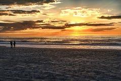 Lyckliga par som går på stranden på soluppgång för ferietid royaltyfri fotografi