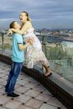 Lyckliga par som går på taket av en hög byggnad, med sikter av storstaden. Flicka som skrattar och att krama vännen. royaltyfria bilder