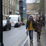 Lyckliga par som går på tegelstengränd i regnet Royaltyfria Bilder