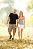 Lyckliga par som går till och med parkera Arkivfoto
