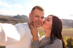 Lyckliga par som gör selfie mot bergen royaltyfri fotografi