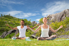 Lyckliga par som gör yoga och utomhus mediterar Fotografering för Bildbyråer