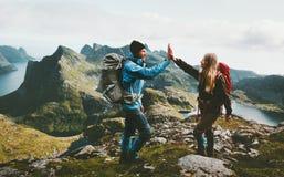 Lyckliga par som ger fem händer som fotvandrar med ryggsäcken royaltyfria bilder