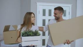 Lyckliga par som håller ögonen på deras nya hem- upphetsat Den unga mannen ger tangenter till hans flickvän och att kyssa henne stock video