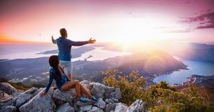 Lyckliga par som håller ögonen på solnedgången i bergen Royaltyfria Foton