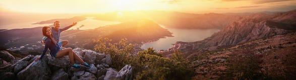 Lyckliga par som håller ögonen på solnedgången i bergen arkivbilder