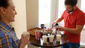 Lyckliga par som har ett mellanmålavbrott som dricker te Royaltyfri Bild