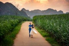Lyckliga par som har gyckel i fältet på solnedgången royaltyfri foto