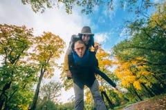 Lyckliga par som har gyckel i höst, parkerar Gula träd och sidor Skratta den utomhus- mannen och kvinnan svart isolerad begreppsf Arkivfoton