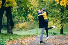 Lyckliga par som har gyckel i höst, parkerar Gula träd och sidor Skratta den utomhus- mannen och kvinnan svart isolerad begreppsf Royaltyfri Fotografi