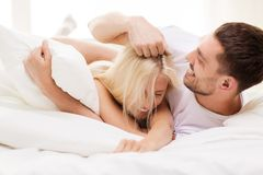 Lyckliga par som har gyckel i säng hemma Arkivbilder