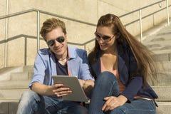 Lyckliga par som har gyckel med minnestavlaPC Arkivbilder