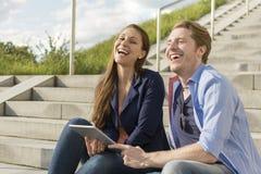 Lyckliga par som har gyckel med minnestavlaPC Arkivfoton