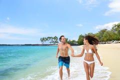 Lyckliga par som har gyckel som kör tillsammans på stranden Arkivfoton