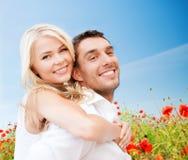 Lyckliga par som har gyckel över vallmoblommafält Fotografering för Bildbyråer