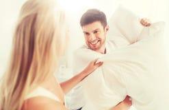 Lyckliga par som har kuddekamp i säng hemma Arkivfoton