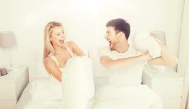 Lyckliga par som har kuddekamp i säng hemma Royaltyfria Bilder