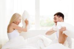Lyckliga par som har kuddekamp i säng hemma Arkivbilder