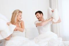 Lyckliga par som har kuddekamp i säng hemma Royaltyfri Bild