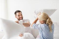 Lyckliga par som har kuddekamp i säng hemma Arkivbild