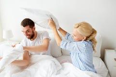 Lyckliga par som har kuddekamp i säng hemma Arkivfoto