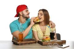 Lyckliga par som har lunch med hamburgare p? tabellen royaltyfri fotografi