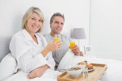 Lyckliga par som har orange fruktsaft på frukosten i säng Arkivfoto