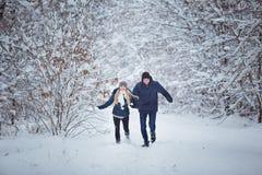 Lyckliga par som har rolig det fria i snö, parkerar snowman för sand för hav för bakgrundsstrand exotisk gjord tropisk semester v Royaltyfria Foton