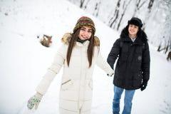 Lyckliga par som har rolig det fria i snö, parkerar snowman för sand för hav för bakgrundsstrand exotisk gjord tropisk semester v Arkivbild