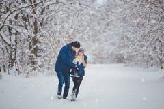 Lyckliga par som har rolig det fria i snö, parkerar snowman för sand för hav för bakgrundsstrand exotisk gjord tropisk semester v Arkivfoton