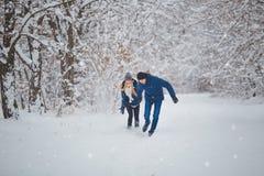 Lyckliga par som har rolig det fria i snö, parkerar snowman för sand för hav för bakgrundsstrand exotisk gjord tropisk semester v Arkivfoto