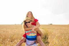 Lyckliga par som har rolig det fria på fält svart isolerad begreppsfrihet piggyback arkivfoton