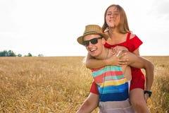 Lyckliga par som har rolig det fria på fält svart isolerad begreppsfrihet piggyback royaltyfri foto