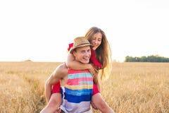 Lyckliga par som har rolig det fria på fält svart isolerad begreppsfrihet piggyback arkivfoto