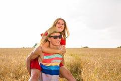 Lyckliga par som har rolig det fria på fält svart isolerad begreppsfrihet piggyback arkivbilder