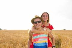 Lyckliga par som har rolig det fria på fält svart isolerad begreppsfrihet piggyback royaltyfria foton