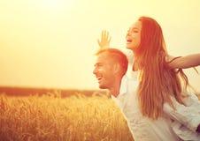 Lyckliga par som har rolig det fria på vetefält Royaltyfri Bild