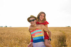 Lyckliga par som har rolig det fria på vetefält Skratta den glade familjen tillsammans svart isolerad begreppsfrihet piggyback royaltyfria bilder