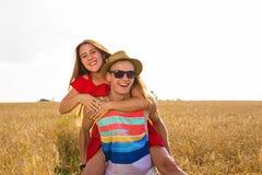 Lyckliga par som har rolig det fria på vetefält Skratta den glade familjen tillsammans svart isolerad begreppsfrihet piggyback arkivfoto