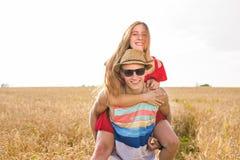 Lyckliga par som har rolig det fria på vetefält svart isolerad begreppsfrihet piggyback royaltyfri fotografi