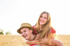 Lyckliga par som har rolig det fria på vetefält svart isolerad begreppsfrihet piggyback royaltyfri bild