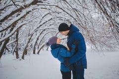 Lyckliga par som har roligt och utomhus omfamnar i snö, parkerar snowman för sand för hav för bakgrundsstrand exotisk gjord tropi Fotografering för Bildbyråer