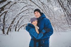 Lyckliga par som har roligt och utomhus omfamnar i snö, parkerar snowman för sand för hav för bakgrundsstrand exotisk gjord tropi Arkivfoto