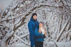Lyckliga par som har roligt och utomhus omfamnar i snö, parkerar snowman för sand för hav för bakgrundsstrand exotisk gjord tropi Royaltyfri Fotografi