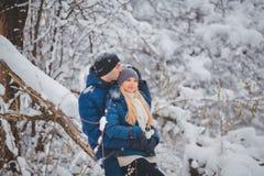 Lyckliga par som har roligt och utomhus omfamnar i snö, parkerar snowman för sand för hav för bakgrundsstrand exotisk gjord tropi Royaltyfri Foto