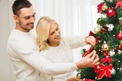 Lyckliga par som hemma dekorerar julträdet Fotografering för Bildbyråer