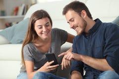 Lyckliga par som hemma kontrollerar smarta telefonapps royaltyfri fotografi