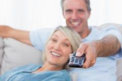 Lyckliga par som hemma kopplar av hållande ögonen på tv Fotografering för Bildbyråer