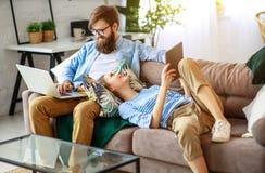 Lyckliga par som hemma kopplar av med bärbara datorn och minnestavlan royaltyfria foton