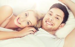 Lyckliga par som hemma ligger i säng Royaltyfria Foton